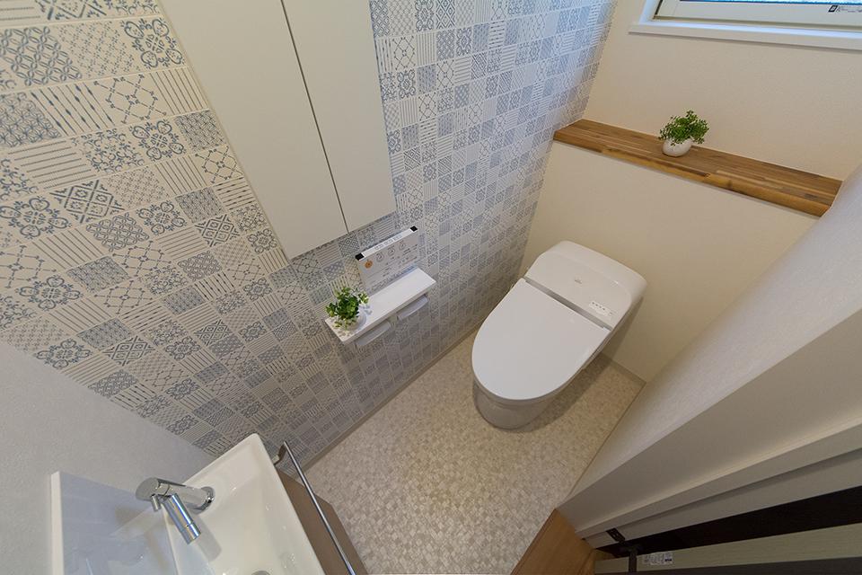 白を基調とした清潔感のある1階トイレ。アクセントクロスが爽やかな印象をプラス。