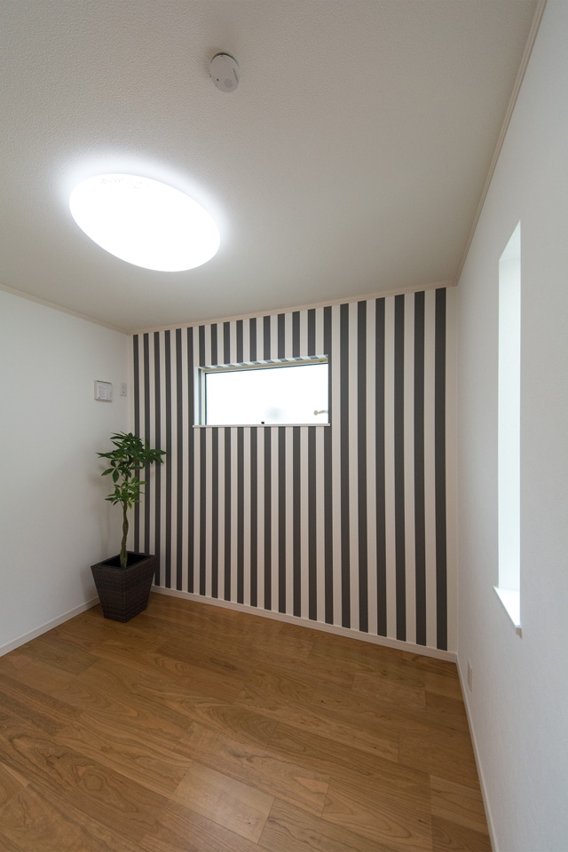 モダンなストライプ柄アクセントクロスが印象的な1階洋室。