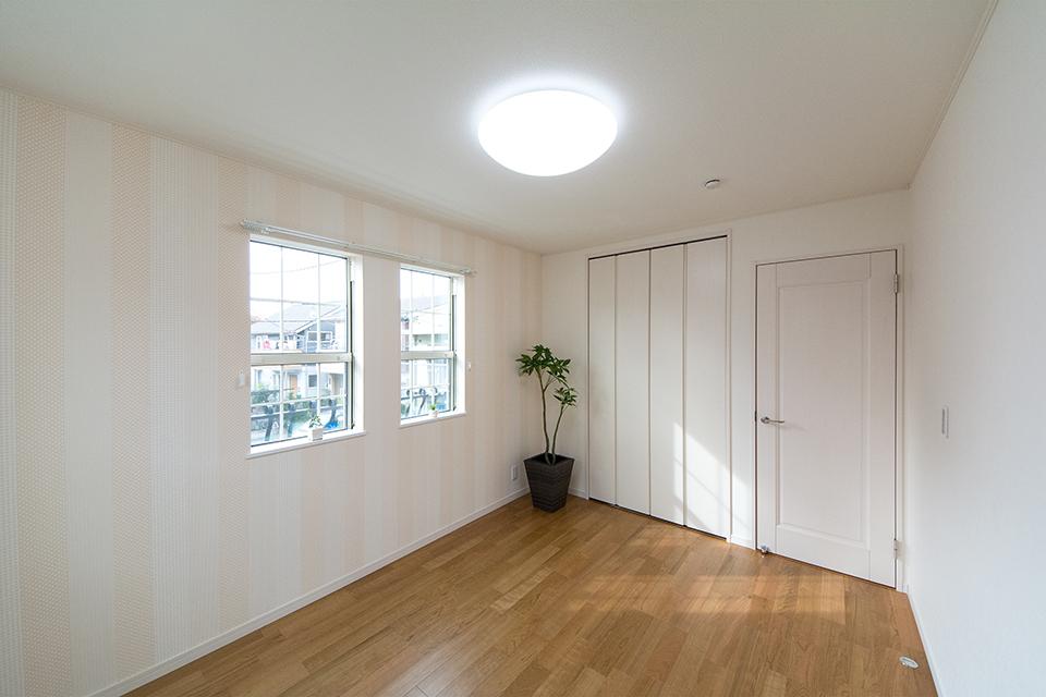 2階洋室。ブラックチェリーのフローリングがナチュラルな空間を演出。ピンクのストライプ柄アクセントクロスが彩りを与えます。