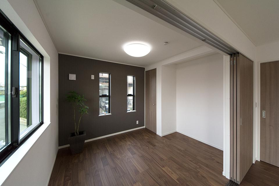 1階洋室B―ダークブラウンのアクセントクロスがモダンな印象をプラス。