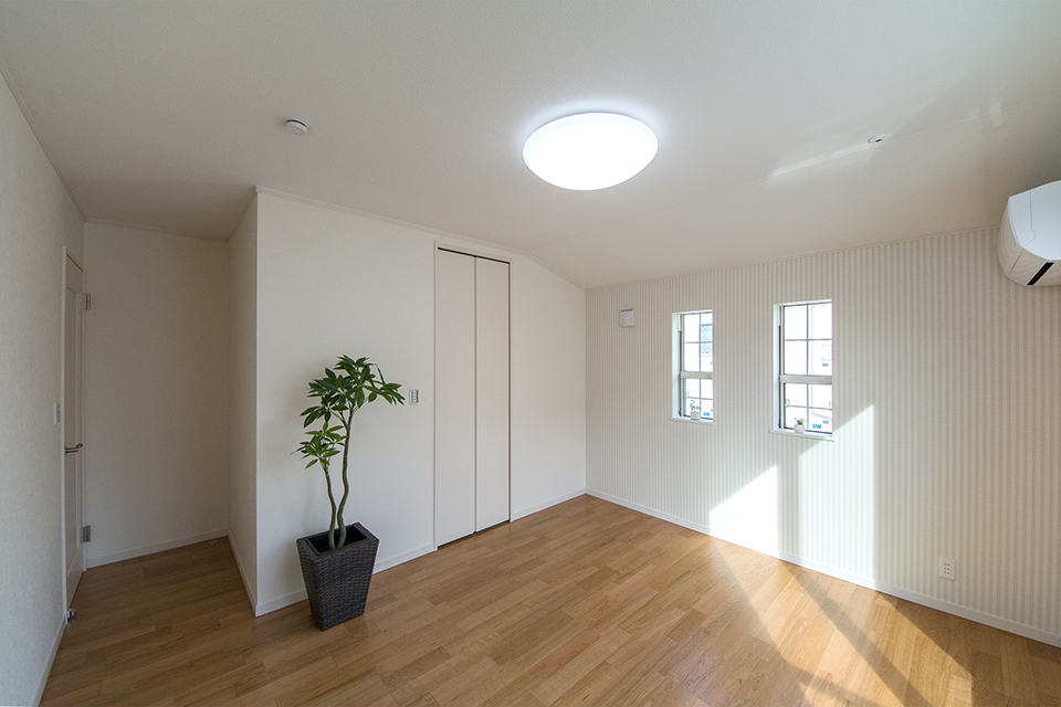 2階洋室。ブラックチェリーのフローリングがナチュラルな空間を演出します。ストライプ柄アクセントクロスが彩りを与えます。