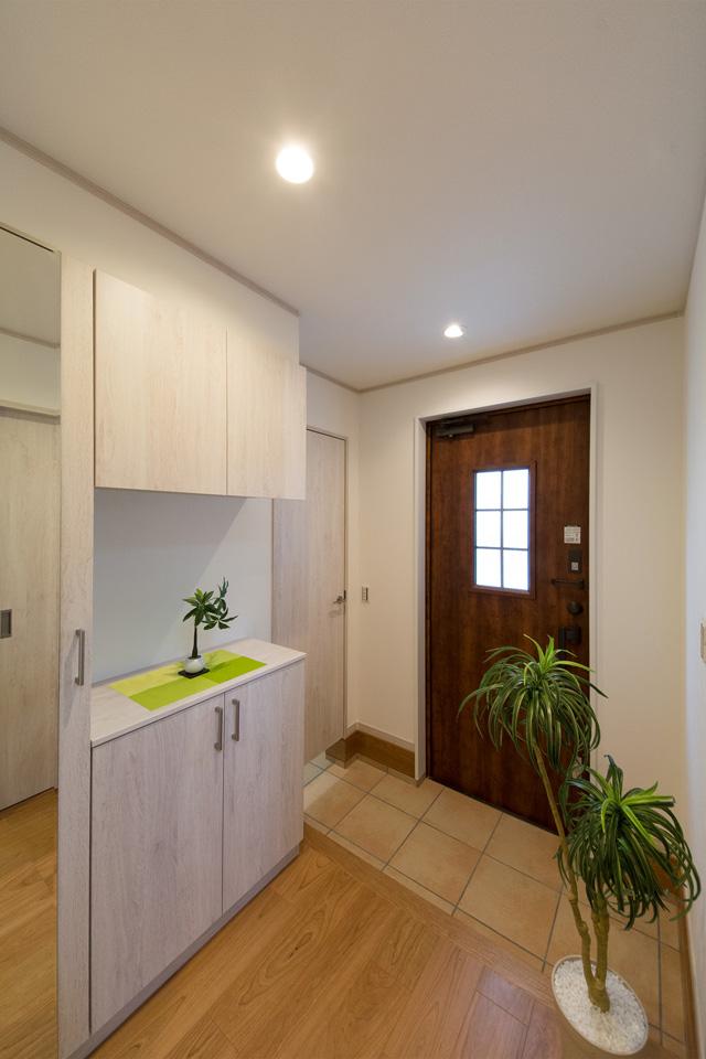 ナチュラルな雰囲気を演出するハンドダウンチェリーの玄関ドア。窓部分から差し込む光が、明るく開放的ある空間を演出。