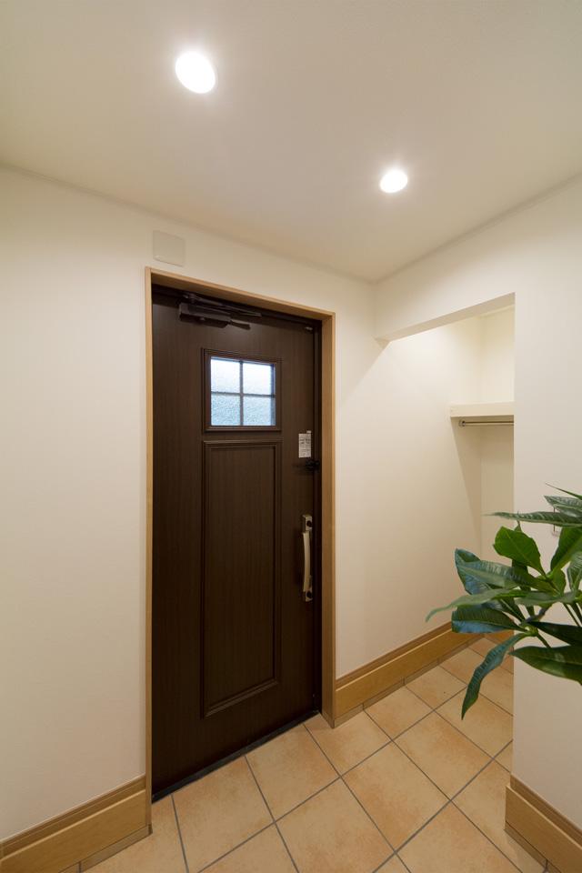 ショコラウォールナットの玄関ドアとベージュのテラコッタ調タイルがナチュラルなエントランス空間を演出。