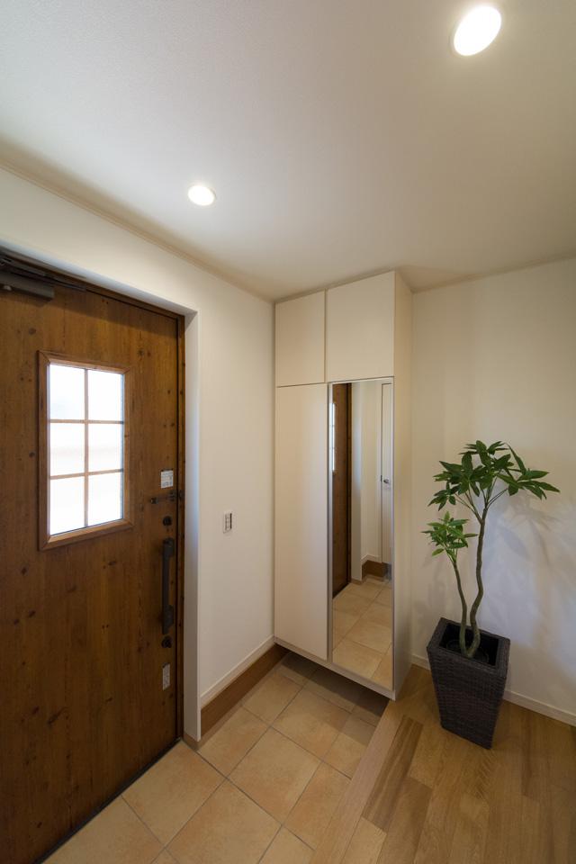 アイリッシュパインの玄関ドアとベージュのテラコッタ調タイルがナチュラルなエントランス空間を演出。