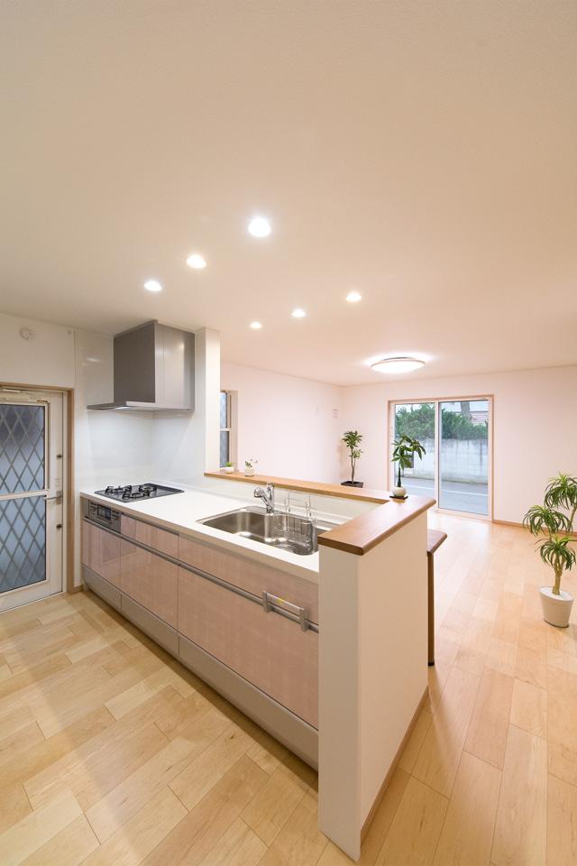 ローズのキッチン扉が爽やかな印象を与えるキッチンスペース。