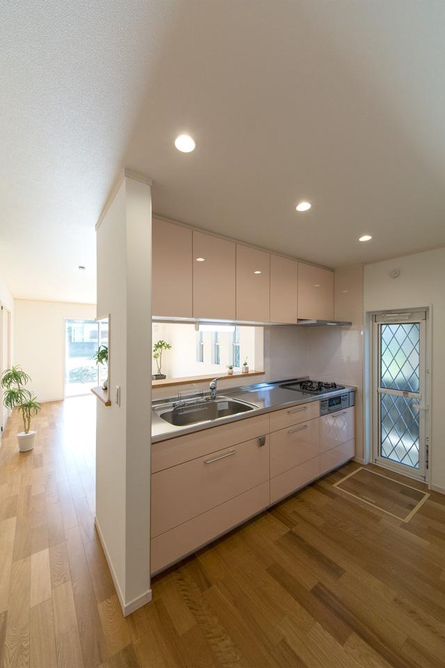ミストピンクのキッチン扉が爽やかな印象を与えるキッチンスペース。