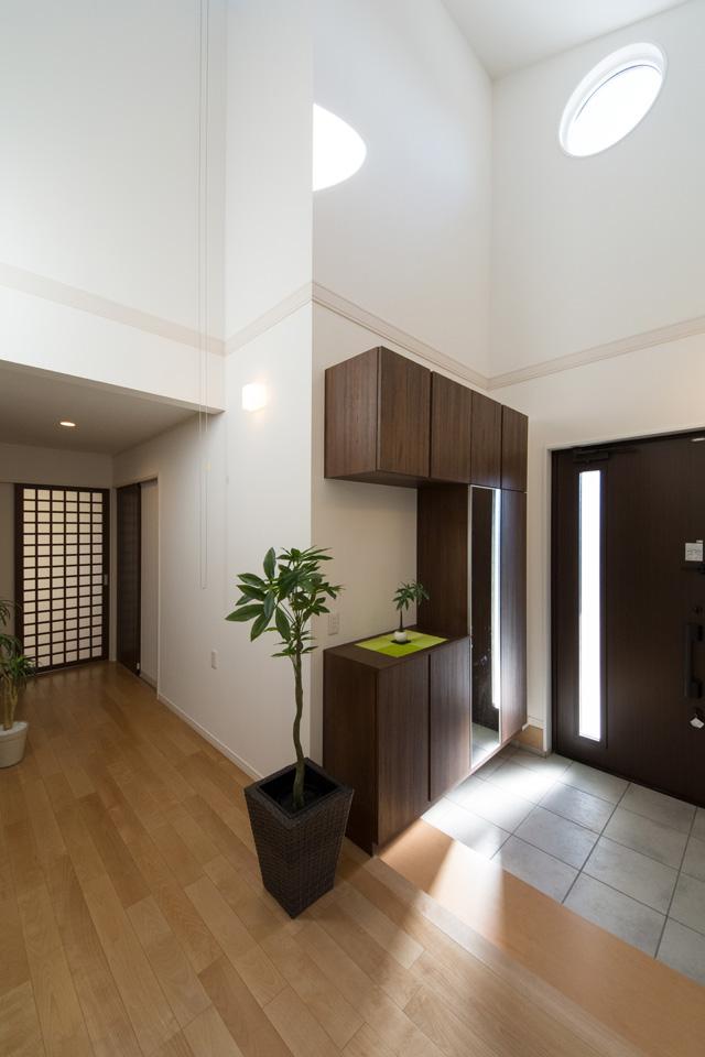 開放感ある勾配天井の玄関。上部の円型窓から自然のやさしい光が降り注ぎ、明るく開放的な空間を演出。