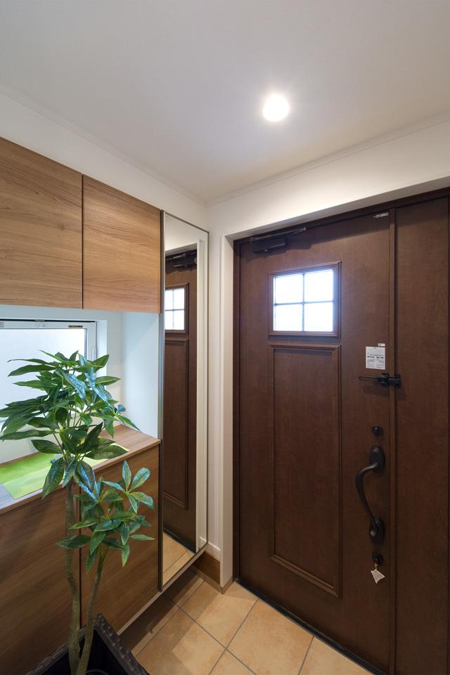 素朴感のあるチーク材をモチーフにした木調色の玄関ドアがナチュラルなエントランス空間を演出。