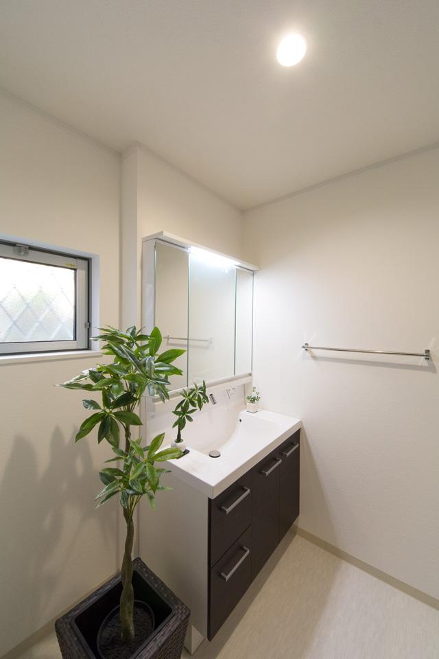 白を基調とした清潔感のあるサニタリールーム。ダークブラウンの洗面化粧台が印象的。