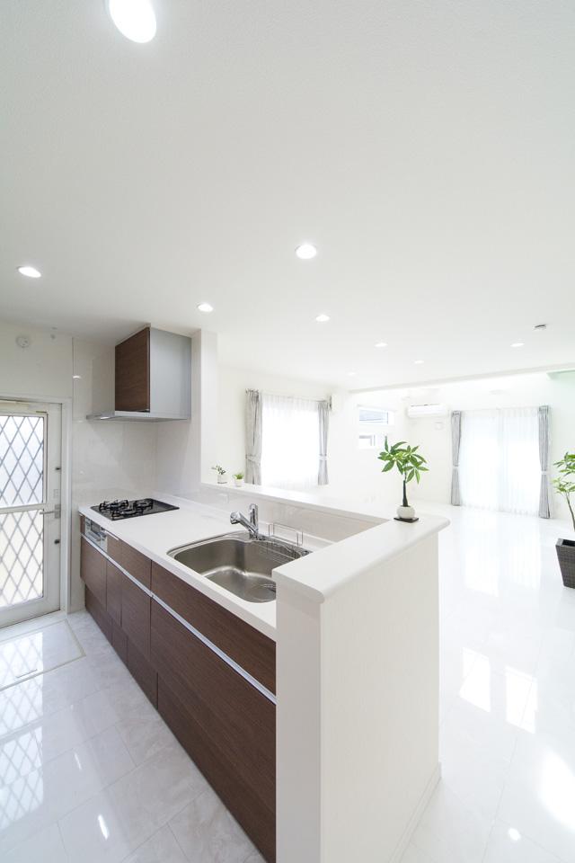 白基調の空間に映えるブラウンのキッチン。