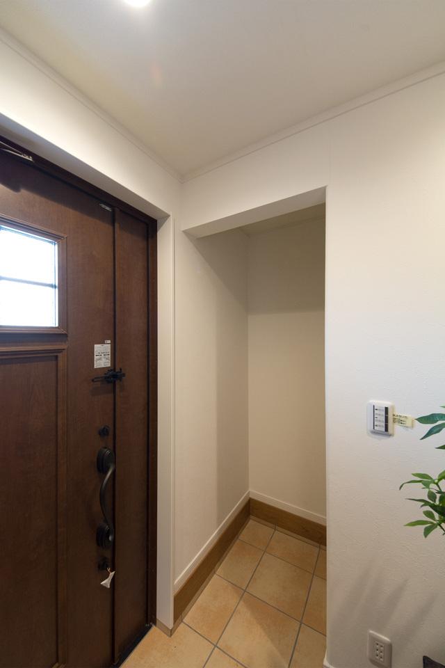 ショコラウォールナットの玄関ドアとベージュのテラコッタ調タイルがナチュラルなベビーカーや傘立てなどが収納できる便利な土間収納を設えた玄関。