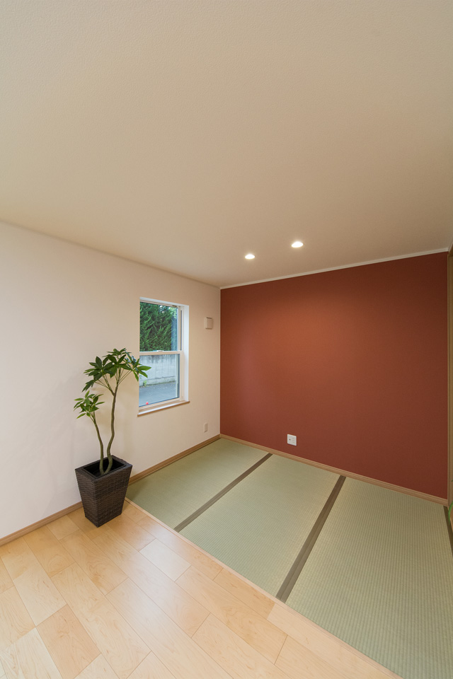 朱色のアクセントクロスが空間を彩る1階畳敷スペース。