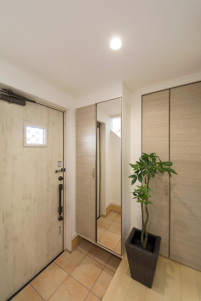 エクリュアイボリーの玄関ドアがナチュラルな空間を演出。