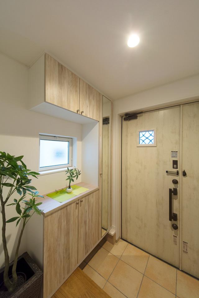 エクリュアイボリーの玄関ドアとベージュのテラコッタ調タイルがナチュラルな空間を演出。