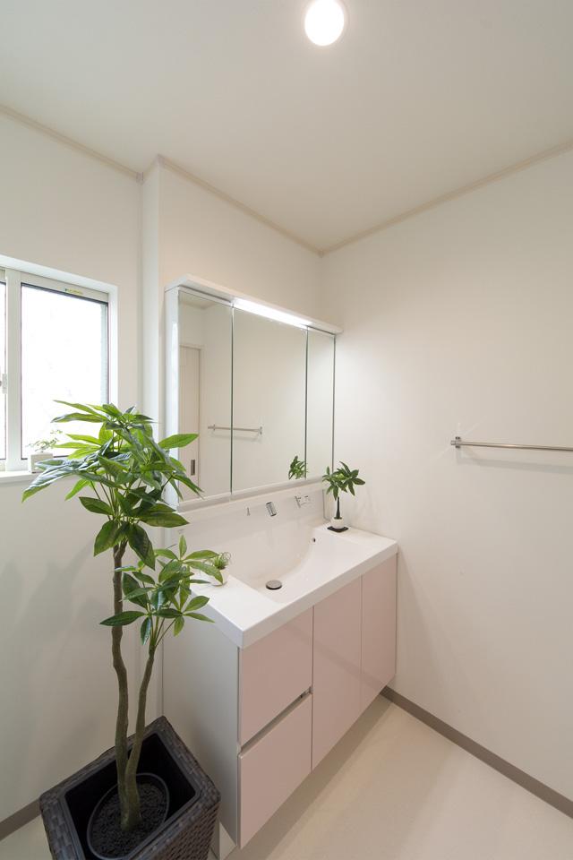 白を基調とした清潔感のあるサニタリールーム。パステルピンクの洗面化粧台が爽やかな印象をプラス。