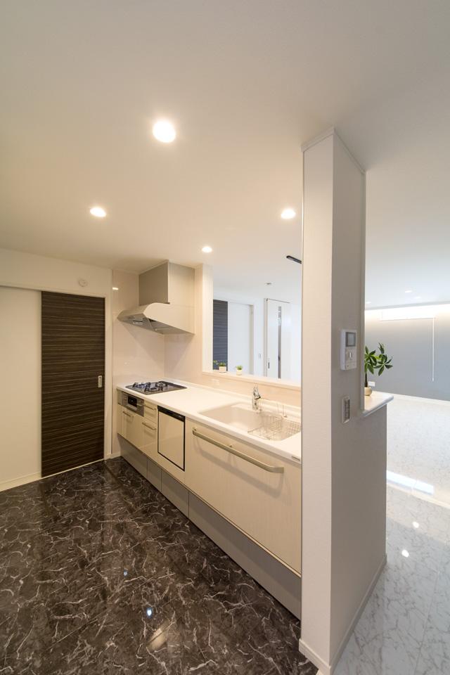 白を基調とした清潔感のあるキッチン。黒の石目柄フロアがモダンな雰囲気を与えます。