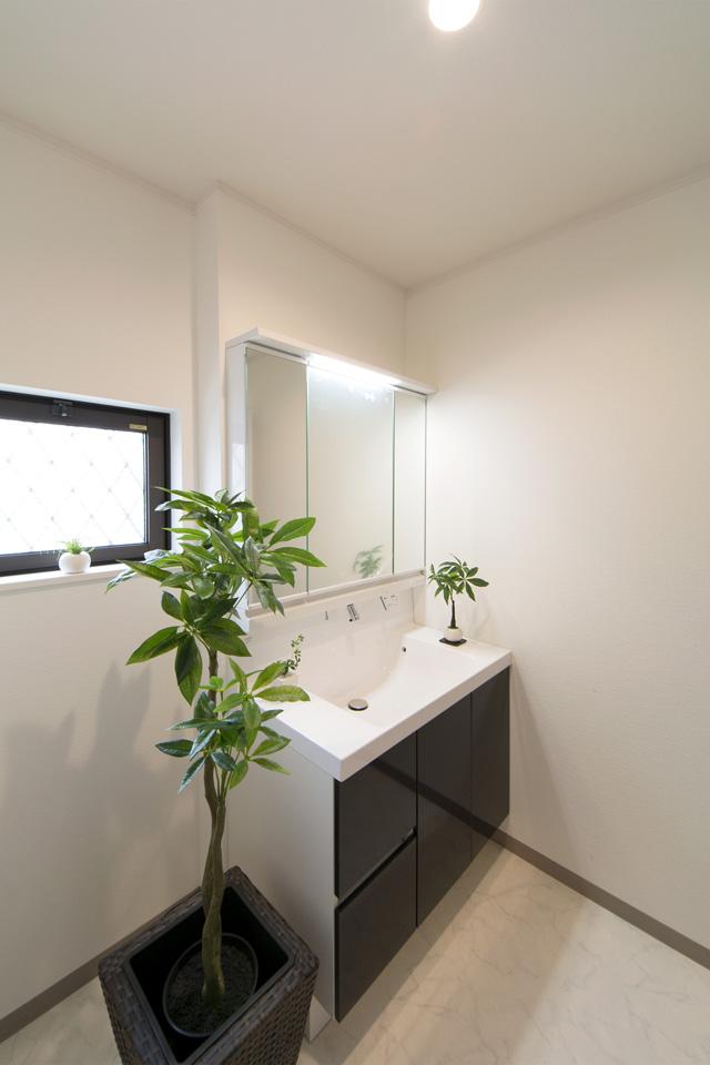 白を基調とした清潔感のあるサニタリールーム。ディープグレーの洗面化粧台が印象的です。