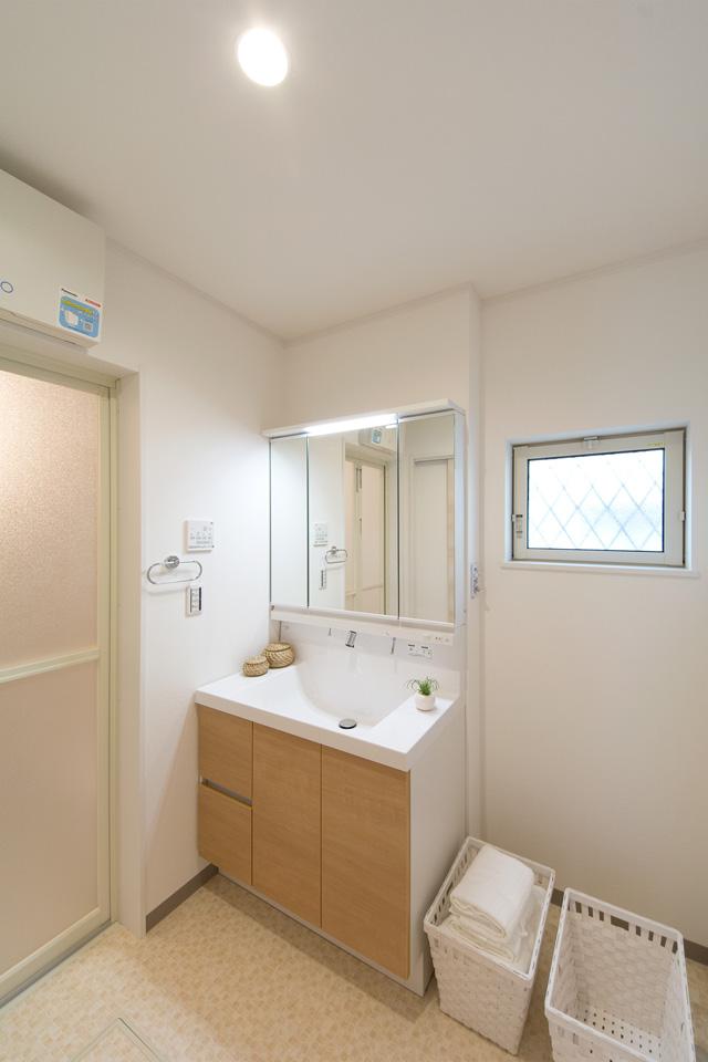 白を基調とした清潔感のあるサニタリールーム。ライトブラウンの洗面化粧台が爽やかな印象をプラス。