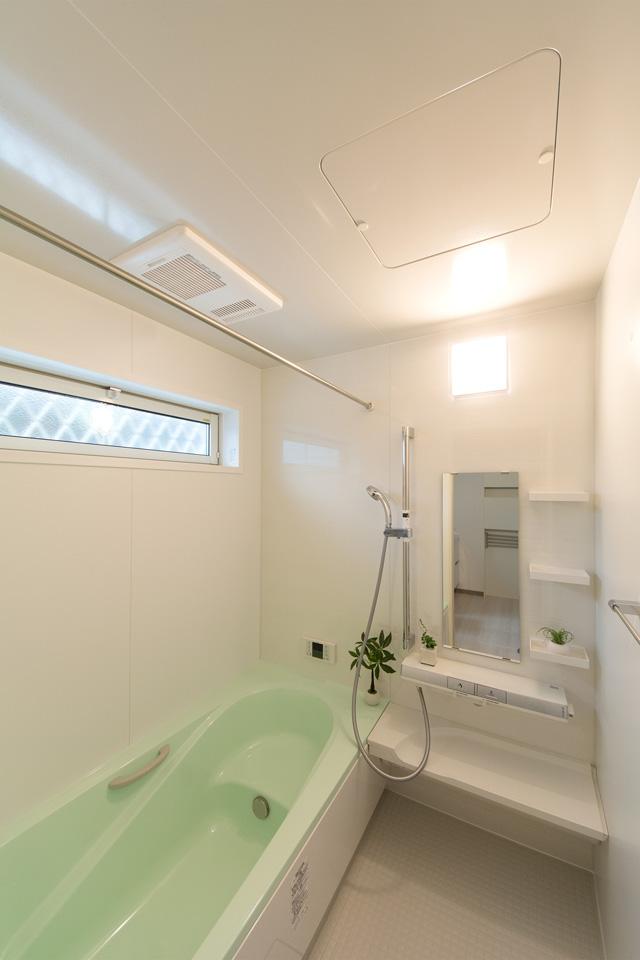 グリーンの浴槽が爽やかな印象を与えるバスルーム。