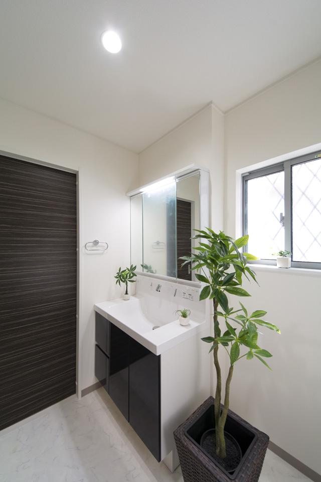白を基調とした清潔感のあるサニタリールーム。ディープグレーの洗面化粧台が印象的。