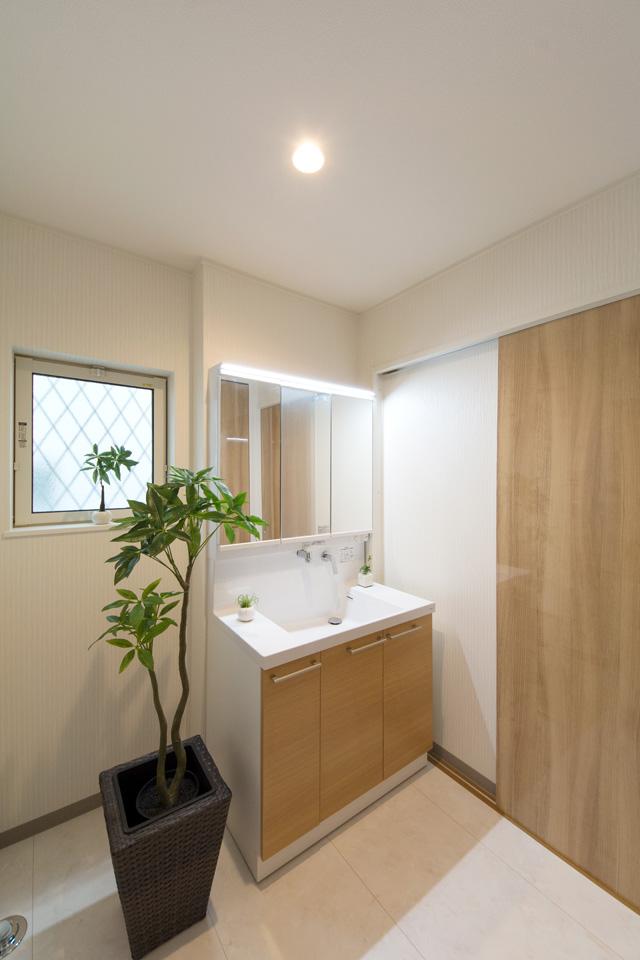 白を基調とした清潔感のあるサニタリールーム。ライトブラウンの洗面化粧台がナチュラルな印象を与えます。