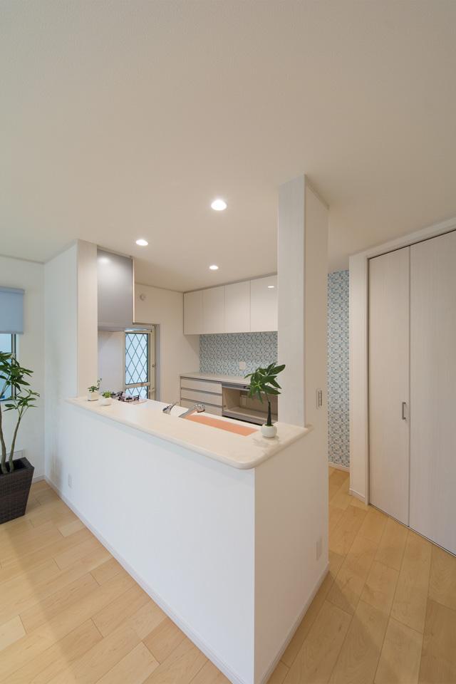 キッチン背面にあしらった水色のアクセントクロスが爽やかな印象を与えます。