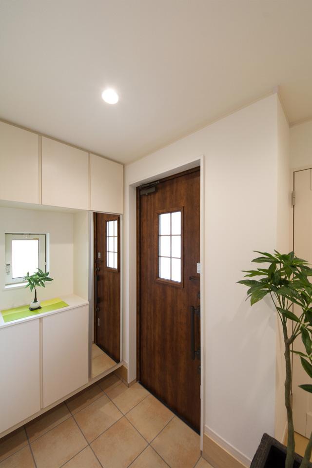 ハンドダウンチェリーの玄関ドアとベージュのテラコッタ調タイルがナチュラルなエントランス空間を演出。