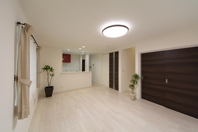 白の床材とダークブラウンの建具が洗練された雰囲気を演出。