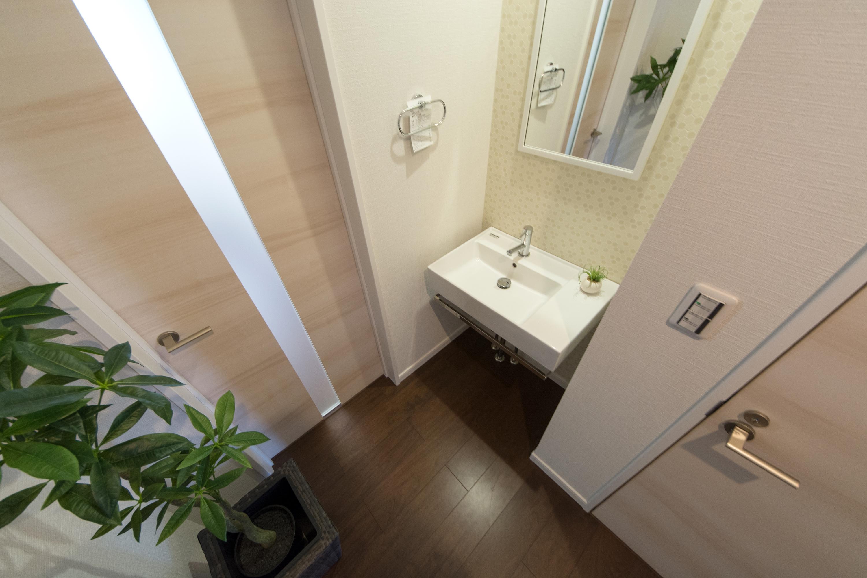 モザイク柄のアクセントクロスが爽やかな印象を与える1階洗面。