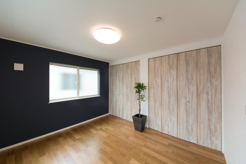 2階洋室/ブラックチェリーのフローリングがナチュラルな空間を演出。ネイビーのアクセントクロスが印象的です。