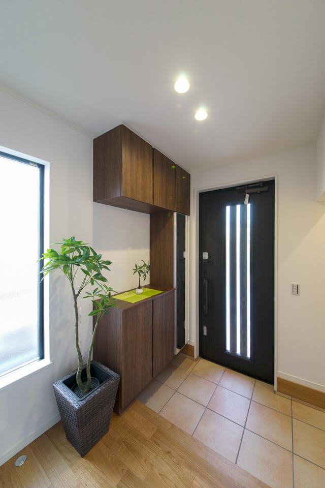 玄関ホール。ドアのストライプと窓の光が明るく照らし、テラコッタ調タイルが落ち着いた雰囲気を演出します。