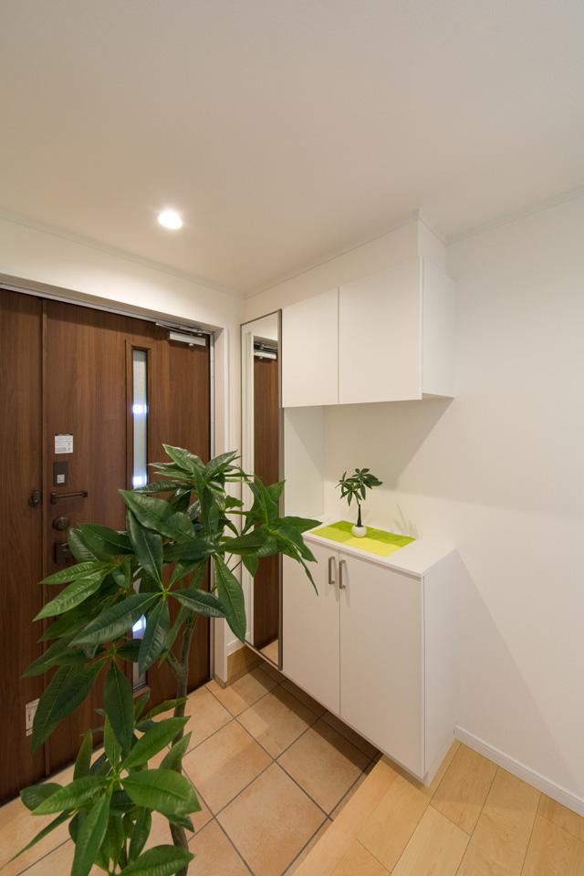 モカ色の玄関ドアとベージュのテラコッタ調タイルがナチュラルなエントランス空間を演出。