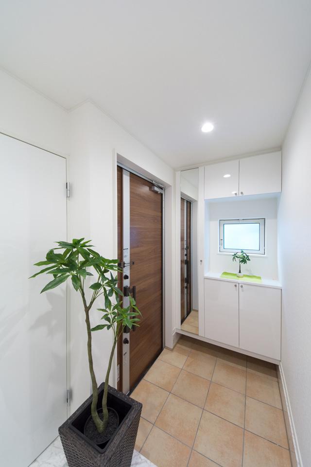 モカ色の玄関ドア、テラコッタ調タイル、小窓の明るい光が、玄関ホールを落ち着いた雰囲気に演出します。