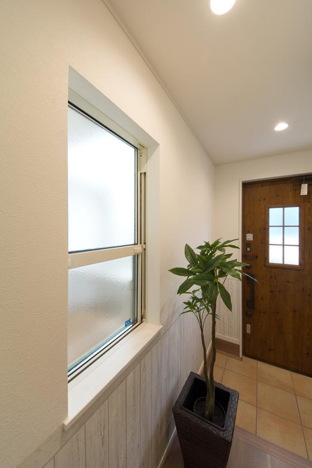 玄関手前の窓からオシャレなウッドデッキを見渡せる