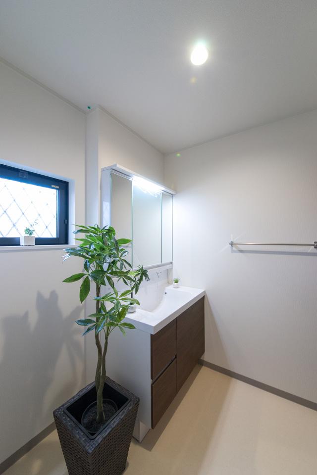 洗面化粧台扉をクリエモカ色でアクセント、清潔感のあるサニタリールーム。
