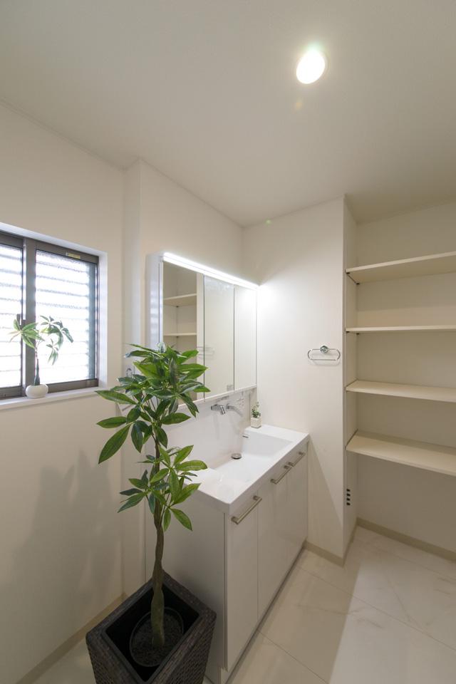 白を基調とした清潔感のあるサニタリールーム。収納したい物によって自由に高さをカスタマイズできる、ダボレール棚を設置しました。