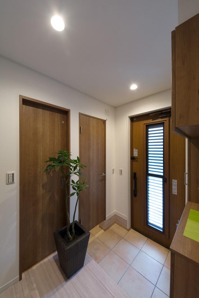 ベビーカーや傘立て、ゴルフバックなどを収納できる便利な扉付土間収納を設えた玄関。