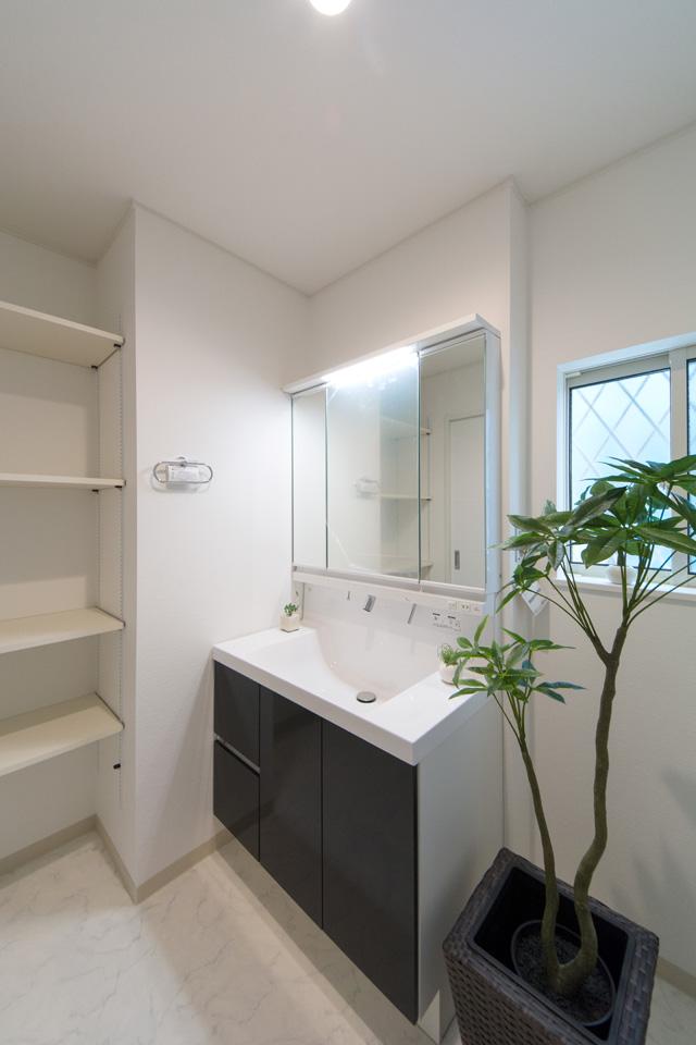 白を基調とした清潔感のあるサニタリールーム。洗面化粧台扉はデイープグレー色でアクセント。可動棚設置で収納スペースも確保しました。