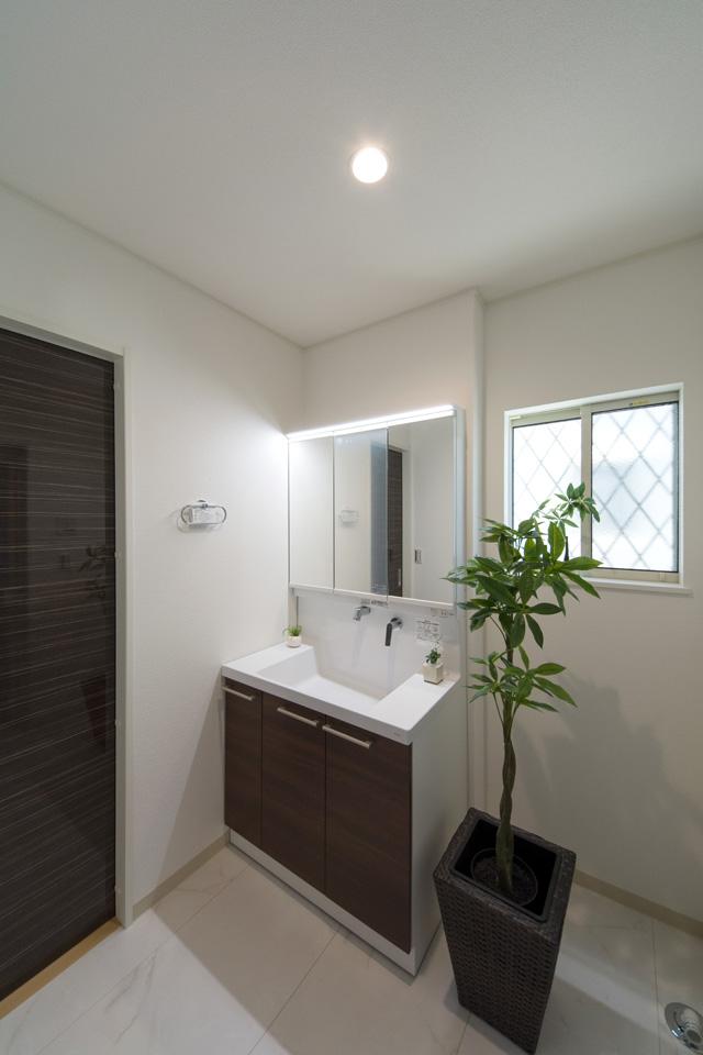洗面化粧台扉をブラウン系の色でアクセント、清潔感のあるサニタリールーム。