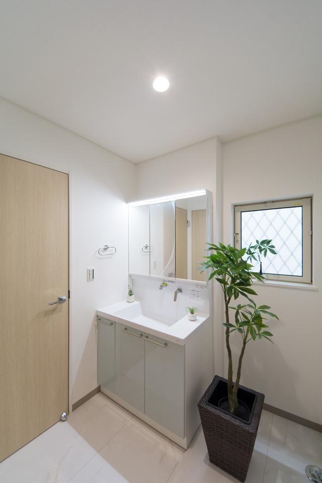 洗面化粧台の扉をパナシェアクア色でアクセント、清潔感のあるサニタリールーム。