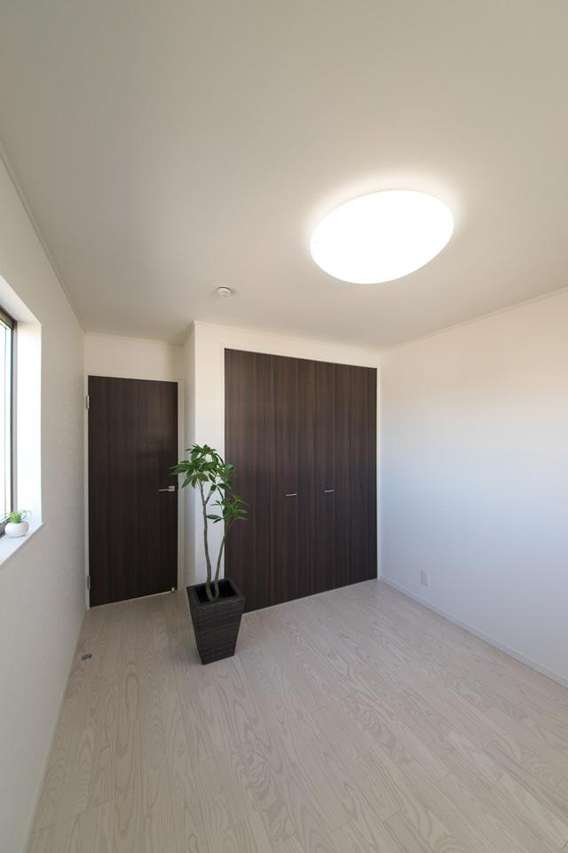 2F洋室。アッシュホワイトのフローリングと木目調ダークブラウンの建具が、スタイリッシュな空間を演出します。
