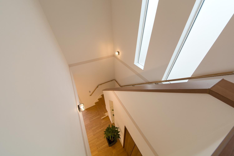 窓の光が差し込む、明るく開放感のある階段。上り下りも手摺があるので安全です。