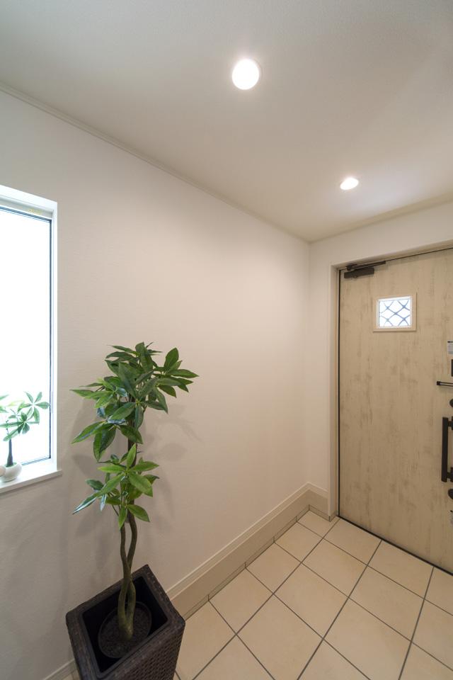 アイボリーの玄関扉とホワイトのテラコッタ調タイルがナチュラルな雰囲気を演出。