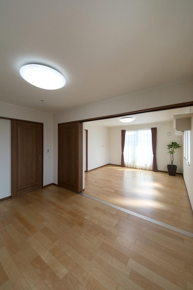 2F洋室。重厚感のある大きな引戸を開けると、北側のお部屋からバルコニーへ一直線。