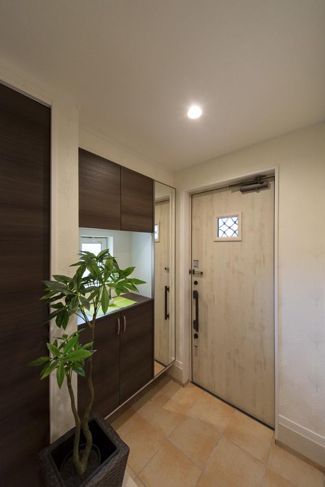 アイボリーの玄関扉とベージュのテラコッタ調タイルがナチュラルな雰囲気を演出。