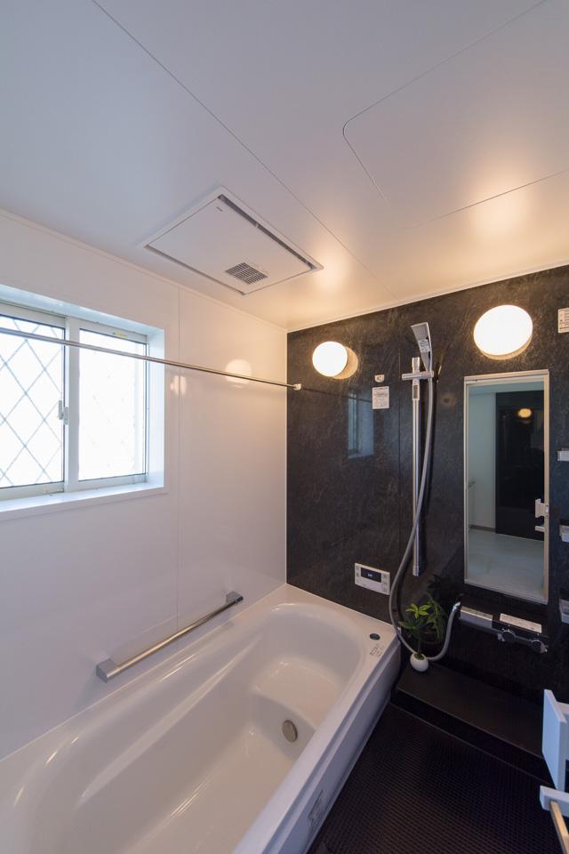 石目柄アースブラックのパネルをアクセントとし、重厚感のある浴室となりました。