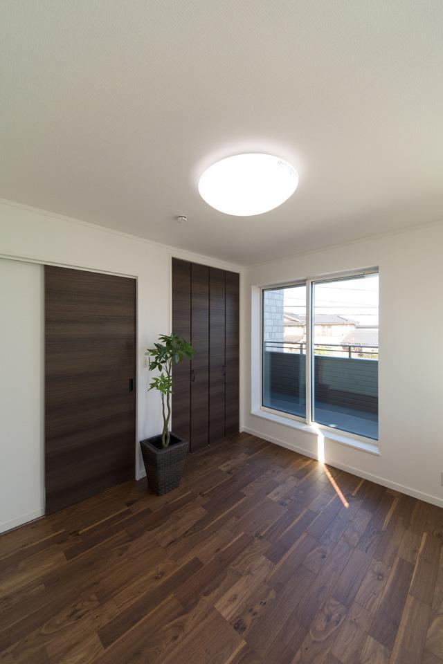 2F洋室。ブラックウォルナットのフローリングとショコラオークのクローゼットが、シックでラグジュアリーな空間を演出します。