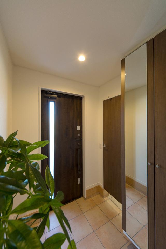 傘立てやゴルフバックなどを収納できる便利な扉付土間収納を設えた玄関。
