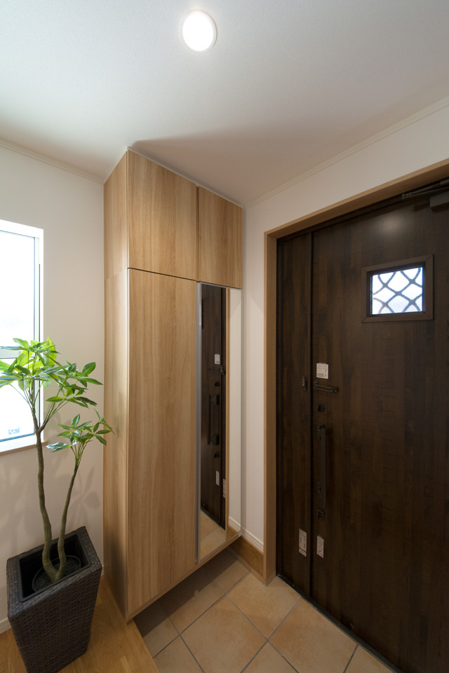 アンティークオークの玄関扉とベージュのテラコッタ調タイルがナチュラルな雰囲気を演出。