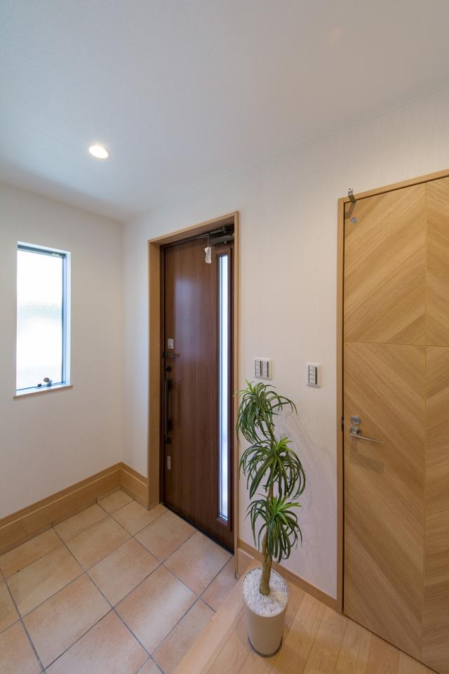 モカ色の玄関扉とベージュのテラコッタ調タイルがナチュラルな雰囲気を演出。